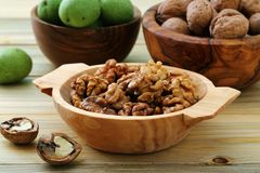 Walnuts green and dry on kitchen table background stock photos