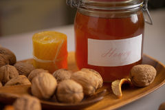 Closeup on walnuts and jar of honey on table Royalty Free Stock Image