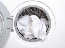 Closeup of washing machine drum and white clean towels royalty free stock photography