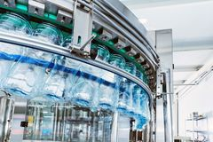 Closeup Water bottling line for processing mineral water. Closeup Water bottling line for processing and bottling pure mineral carbonated water into bottles and stock image