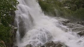 Closeup water drop and spray of a waterfall of a stormy mountain river in a green forest in slow motion with tracking