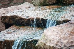Closeup of water running down a couple of rocks stock photography