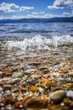 Closeup of Waves Rolling into Beach Shoreline Stock Photo