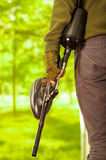 Closeup weapon with magazine held by man standing, forest background, paintball concept Royalty Free Stock Photo