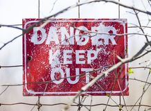 Closeup of weathered red Danger Keep Out sign posted to wire fen Stock Photography