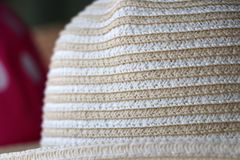 Closeup, Weave hat on horizontal Stripes of Beige and white color royalty free stock photo
