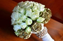 White roses on wedding bouquet. Closeup wedding bouquet made by white roses against brown background Royalty Free Stock Photo