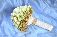 White wedding bouquet against blue background. Closeup wedding bouquet made by white roses on the blue fabric Royalty Free Stock Photo