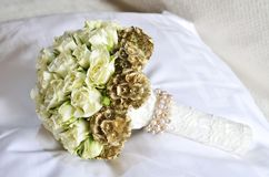 White wedding bouquet on the pillow. Closeup wedding bouquet made by white roses at pillow on the bed Royalty Free Stock Image