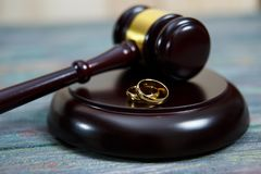 Closeup of wedding rings on wooden mallet at table. In courtroom royalty free stock photography