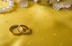 Closeup of wedding rings on the yellow tablecloth Royalty Free Stock Photography