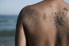 Young man on the beach. Closeup of the wet back of a young caucasian spotted of sand in front of the ocean Royalty Free Stock Images