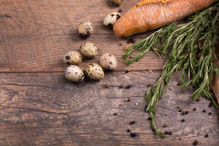 Closeup of wheat baguette, twigs of aromatic rosemary, fragrant seasonings and little quail eggs on a wooden background. Stock Photo