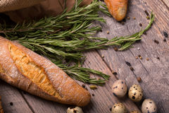 Closeup of wheat baguette, twigs of fragrant rosemary, speckled quail eggs, seasonings on a light wooden background. Stock Images