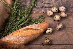 Closeup of wheat baguette, twigs of fragrant rosemary, speckled quail eggs, seasonings on a light wooden background. Stock Image