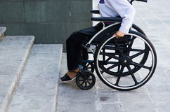 Closeup wheels of wheelchair with woman sitting in it, physical handicapped concept.  Royalty Free Stock Photography