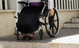 Closeup wheels of wheelchair with woman sitting in it, physical handicapped concept.  Royalty Free Stock Photos