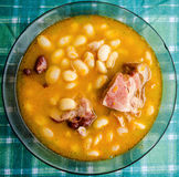 Closeup of white bean soup. Plate with smoked pork leg Stock Image