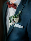 Closeup of white boutonniere pinned to groom`s green jacket Stock Photography