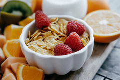 Closeup White bowl with corn Flakes and milk  and Fresh sliced f. Ruit: raspberry, kiwi, melon, oranges on a wooden background Royalty Free Stock Image