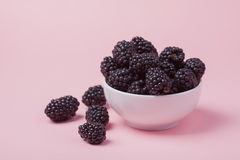 Closeup of a white bowl of fresh red raspberries on a pink background. Copy space.  Stock Photography