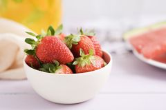 Strawberries and orange juice. Closeup of a white ceramic bowl with strawberries on a table and a glass jar with orange juice and some slices of watermelon in Stock Images