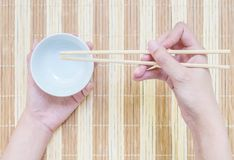 Closeup white ceramic chalice with blurred wood chopsticks in woman hand on wood mat textured background on dining table in top. Closeup white ceramic chalice stock image