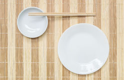 Closeup white ceramic dish and chalice with wood chopsticks on wood mat textured background on dining table in top view Royalty Free Stock Photo