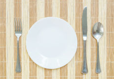 Closeup white ceramic dish with stainless fork and spoon and knife on wood mat textured background on dining table in top view. White ceramic dish with stainless Royalty Free Stock Photography