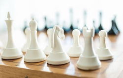 Closeup of white chess piece set on wooden board Stock Photo