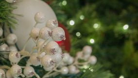 Closeup White Christmas Ornaments On Tree With Blurred Lights In Frame. Closeup of white Christmas Ornaments On Tree with blurred tree branches and lights in royalty free stock image
