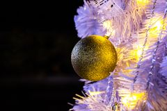 Closeup of white Christmas-tree with golden ball hanging decorations with golden lights glowing. royalty free stock photos