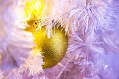 Closeup of white Christmas-tree with golden bauble hanging decor stock photography