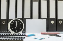Closeup white clock for decorate in 7 o`clock desk of officer with work paper and document file in office room textured backgroun. Closeup clock for decorate in royalty free stock images