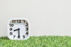 Closeup white clock for decorate show a half past eight or 8:30 a.m. on green artificial grass floor and cream wallpaper textured Stock Photos