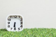 Closeup white clock for decorate show a half past six or 6:30 a.m. on green artificial grass floor and cream wallpaper textured ba. Ckground royalty free stock images