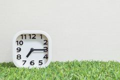 Closeup white clock for decorate show a quarter past seven or 7:15 a.m. on green artificial grass floor and cream wallpaper textur. Closeup white clock for stock photos