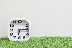 Closeup white clock for decorate show a quarter past six or 6:15 a.m. on green artificial grass floor and cream wallpaper textured stock photography
