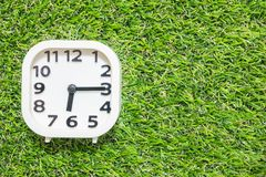 Closeup white clock for decorate show a quarter past six or 6:15 a.m. on green artificial grass floor textured background with cop Stock Image