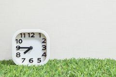 Closeup white clock for decorate show a quarter to eight or 7:45 a.m. on green artificial grass floor and cream wallpaper textured royalty free stock images
