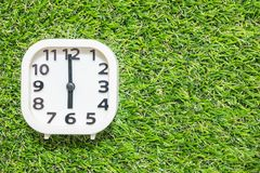 Closeup white clock for decorate in 6 o`clock on green artificial grass floor textured background with copy space Stock Photos