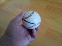 Closeup and of a white cricket hard ball in hand stock photos