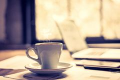 Closeup white cup of coffee break in the work space. Royalty Free Stock Image