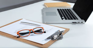 Closeup of white desktop with laptop, glasses, coffee cup, notepads and other items on blurry city background Royalty Free Stock Photos