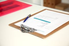 Closeup of white desktop with notepads, pen, coffee cup and other items. Selective focus. Royalty Free Stock Image