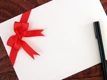 White envelope of greeting card with red ribbon bow and black pen on dark brown wooden table floor. Close-up top view Stock Photo