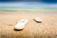 Closeup of white flip flops lying on empty sandy beach Royalty Free Stock Photo