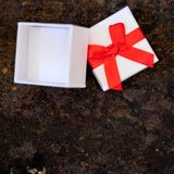 Closeup, white gift box with red ribbon on rusty table Royalty Free Stock Photos