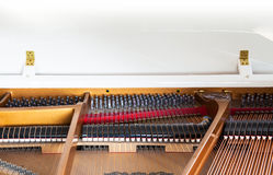 Closeup of white grand piano showing the strings, pegs and sound Royalty Free Stock Photography