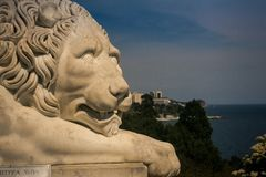Closeup White Marble Lion Head Sculpture against Black Sea in Crimea. Closeup head of old white marble lion sculpture in Vorontsov palace park in springtime royalty free stock photography